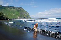 A young local mother and her toddler play in the waves at the black sand beach of Waipi'o Valley, Island of Hawai'i.