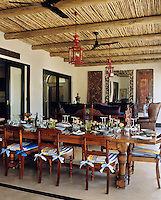 A long table is laid for lunch under an old-fashioned ceiling fan and a Chinese lantern on the covered terrace of a country house hotel in Africa