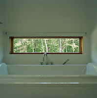 A ribbon window running the length of the bath affords a panoramic view of the surrounding woods