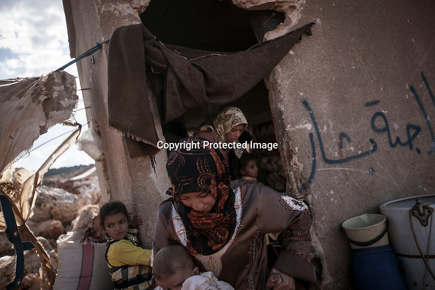 In this Sunday, Sep. 22, 2013 photo, Syrian internal displaced women take care of their children outside an abandoned structure in a no man's land where they have taken shelter after have fled from Kafr Nabudah village, their homeland turned into a battlefield where clashes between troops loyal to president Bashar Al-Assad and opposition fighters have broken out as many opposition armed groups launched a coordinated attack over the Syrian army positions in the Idlib province countryside, Syria. (Photo/AP).