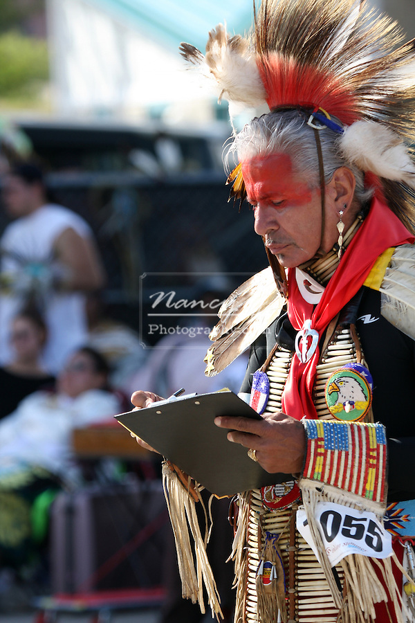 A Native American Indian judge who is judging and recording scores during the dancing at a Pow Wow at the Milwaukee Lakefront Indian Summer Festival, Wisconsin