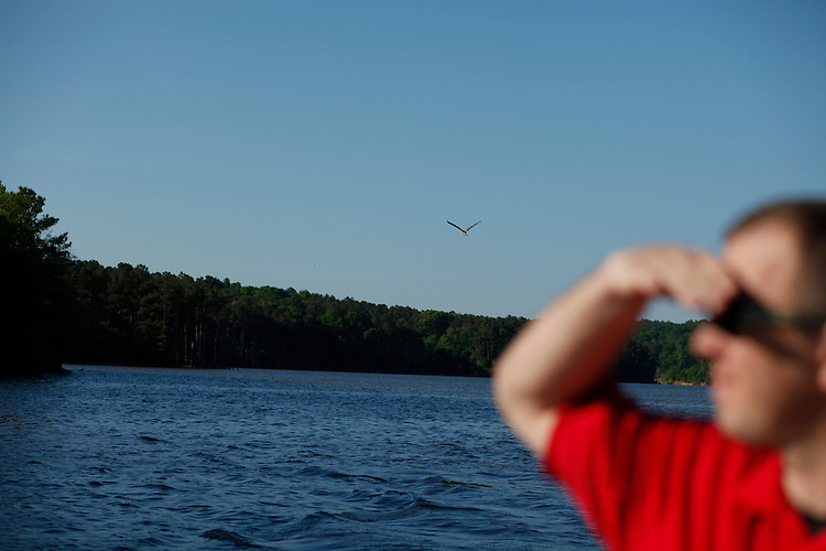Tom Colson is working to organize a trash clean-up effort of Jordan Lake, Tues., April 27, 2010. Colson surveys the shoreline of Jordan Lake as a blue heron flies overhead.