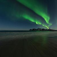 Northern lights - Aurora Borealis fill sky over Storsandnes beach, Flakstadøy, Lofoten Islands, Norway