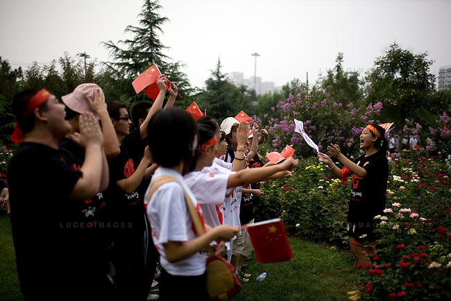 Chinese Olympic fans show their support while waiting for the opening ceremony fireworks in Beijing, China on Friday, August 8, 2008.  Kevin German