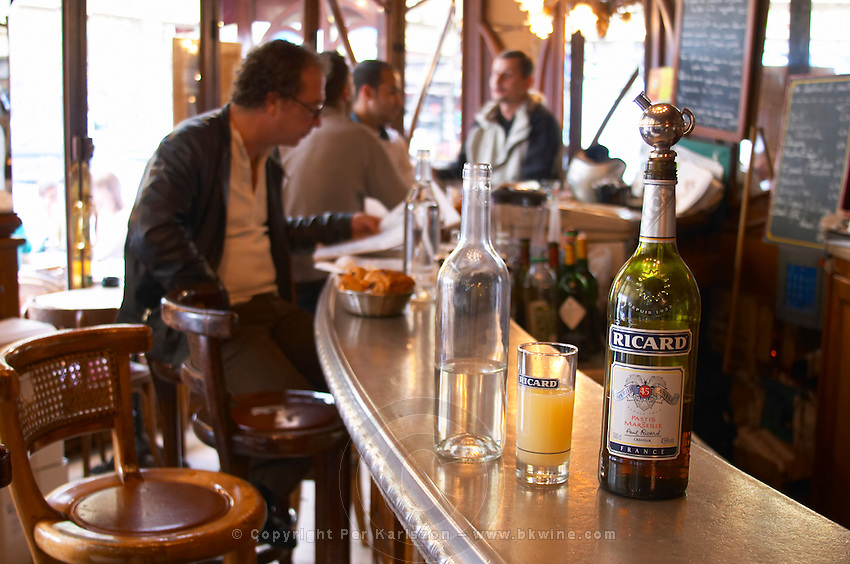 A bottle of Ricard 45 pastis and a glass and a carafe of water on a zinc bar in a cafe bar in Paris. In the background people sitting drinking and eating at the bar Pastis is a spirit high alcohol drink flavoured flavored with herbs such as anise (badiane, anis étoilé etoile) and other spices. It is sometimes called pastis or Absinth absinthe. It is served in a tall glass with ice and you pour water on it. It gets cloudy milky when water is added. It is a favourite drink aperitif in Provence Southern France. The curved bar zinc brass beer and water taps and water carafes blurred people sitting on high chairs drinking Bottles and glasses on shelves behind the bar. The Bistrot du Peintre is an old fashioned Paris café cafe bar restaurant of art nouveau design with polished brass, mirrors and old signs
