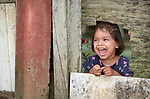 An indigenous girl laughs as she looks through a hole in a fence in the Nacoes Indigenas neighborhood in Manaus, Brazil. The neighborhood is home to members of more than a dozen indigenous groups, many of whose members have migrated to the city in recent years from their homes in the Amazon forest.