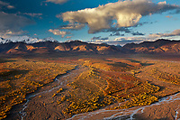 Morning sunshine falls across the Polychrome mountains highlighting the brightly colored autumn tundra, Denali National Park