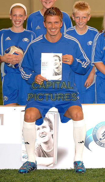 "DAVID BECKHMAM.Real Madrid footballer and ex-England captain promotes his new book ""Making it Real"" at his football academy, London, England, 18th September 2006..The book is his third in five years this new title covers his life since his last book ""My Life"" which was the biggest-selling autobiography of 2004. .full length blue adidas sports top shorts holding book sitting white socks kit football.Ref: BEL.www.capitalpictures.com.sales@capitalpictures.com.©Tom Belcher/Capital Pictures."