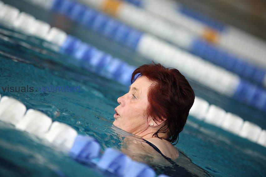 Senior woman swimming in indoor swimming pool
