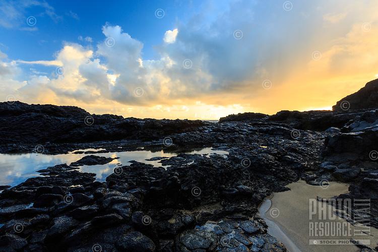 The morning sky fills with light  above the volcanic rock shelf at Lumaha'i Tourist Beach (or Tourist Lumahai) Beach, Kaua'i.