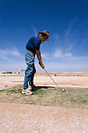 Teeing off at the Coober Pedy Opal Fields Golf Club.  The unique desert course is completely grassless with fairways of bare earth and putting greens made from oiled sand.  Coober Pedy, South Australia, AUSTRALIA.