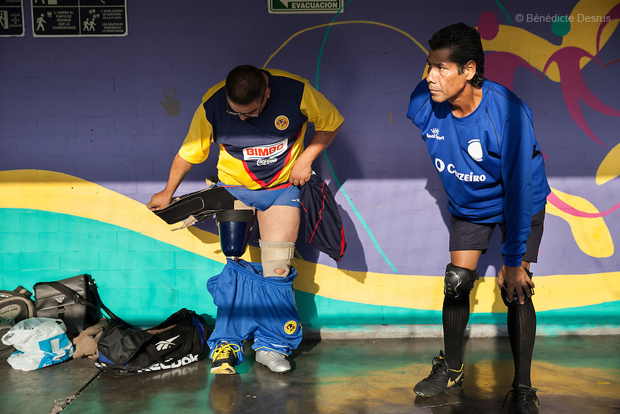"""(L-R) Jose Luis Almaraz Mendoza and Martin Alvarez Olvera, both players from Guerreros Aztecas, get changed before training in Mexico City, Mexico on June 12, 2014. Jose Luis, 32, was washing the windows of his home when he fell 3 metres and lost his right leg. Martin, 49, lost his left arm to a disease of the nerves. He is the team's goalkeeper and is currently unemployed. Guerreros Aztecas (""""Aztec Warriors"""") is Mexico City's first amputee football team. Founded in July 2013 by five volunteers, they now have 23 players, seven of them have made the national team's shortlist to represent Mexico at this year's Amputee Soccer World Cup in Sinaloathis December.The team trains twice a week for weekend games with other teams. No prostheses are used, so field players missing a lower extremity can only play using crutches. Those missing an upper extremity play as goalkeepers. The teams play six per side with unlimited substitutions. Each half lasts 25 minutes. The causes of the amputations range from accidents to medical interventions – none of which have stopped the Guerreros Aztecas from continuing to play. The players' age, backgrounds and professions cover the full sweep of Mexican society, and they are united by the will to keep their heads held high in a country where discrimination against the disabled remains widespread.(Photo byBénédicte Desrus)"""