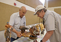 NWA Democrat-Gazette/BEN GOFF @NWABENGOFF<br /> Don Effinger (left) of Bella Vista shows one of his carvings to Ed Ennis of Bella Vista Saturday, July 15, 2017, during the Bella Vista Woodcarvers Club's Artistry in Wood Show at Bella Vista Assembly of God church. Members of the club exhibited and sold their woodwork at the show, which also included door prizes, demonstrations and a people's choice award.