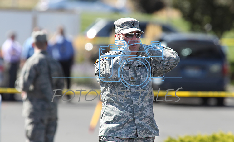 A Nevada National Guard members walks around the command center at the scene of a shooting at an IHOP restaurant in Carson City, Nev., on Tuesday, Sept. 6, 2011. Three people were killed, including two guard members, and six more were injured. (AP Photo/Cathleen Allison)