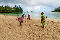 Kanak (Melanesian) boys and girls playing soccer on the beach at Mebuet, island of Mare, Loyalty Islands, New Caledonia