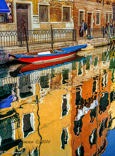 Brightly colored building reflect they're beauty in the canals of Venice, Italy..