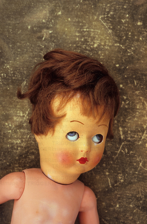 Vintage doll with slightly faded head dishevelled brown hair and eyes rolled upwards lying on scuffed leather