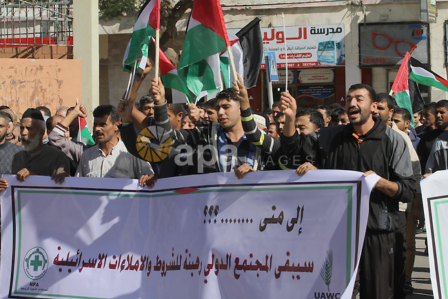 Palestinians hold banners during a protest to demand for reconstruction of the houses which were destroyed by Israeli shelling during the most recent conflict between Israel and Hamas, in Gaza city, Nov. 9, 2014. Photo by Mohammed Asad