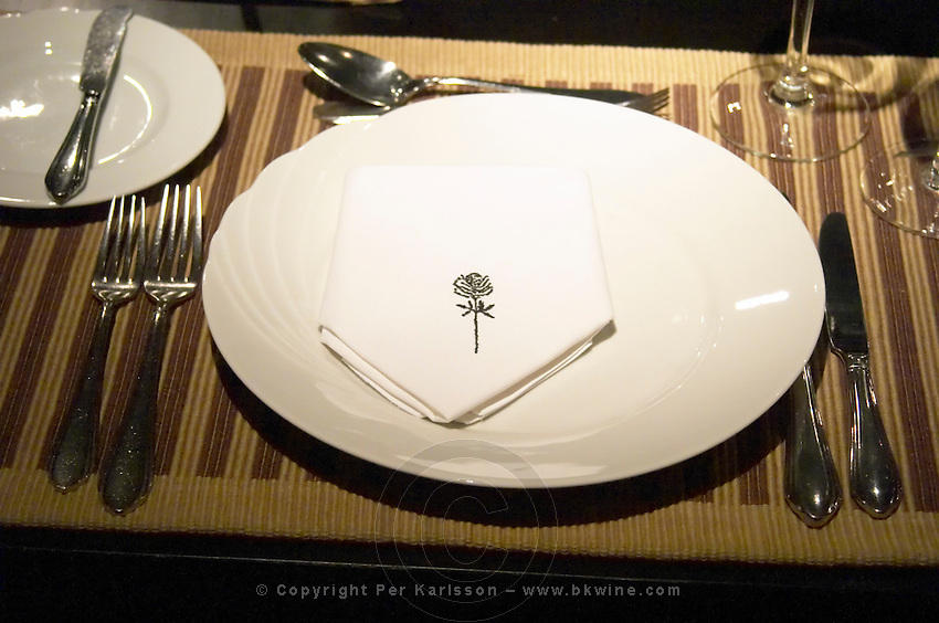 A place set for dinner guest with white plate, linen napkin with black rose, silverware knives and forks, spoons wine glasses. The Rosa Negra Restaurant, The Black Rose, Buenos Aires Argentina, South America
