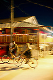 BELIZE, Caye Caulker, tourists ride their bikes in front of Habaneros Restaurant