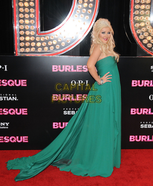 "CHRISTINA AGUILERA.at The Screen Gems' L.A. Premiere of ""Burlesque"" held at The Grauman's Chinese Theatre in Hollywood, California, USA,  November 15th, 2010                                                                                .full length strapless green dress hands on hips long maxi bracelets side train .CAP/RKE/DVS.©DVS/RockinExposures/Capital Pictures."
