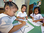 "In the capital of the Philippines, girls who live in the Manila North Cemetery enjoy drawing in class at the Santa Mesa Heights United Methodist Church. Hundreds of poor families live in the cemetery, inside and between the tombs and mausoleums of the city's wealthy. They are often discriminated against, and many of their children don't go to school because they're too hungry to study and they're often called ""vampires"" by their classmates. With support from United Methodist Women, KKFI provides classroom education and meals to kids from the cemetery at this church."