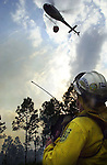 "Division of forestry Fire Boss, Ray Durham directs the approach of the Flagler County Emergency Services helicopter ""FIREFLIGHT"" during a water drop on a training fire along US-1 north of Bunnell, Fla., Friday, March 1, 2002.(Brian Myrick)"