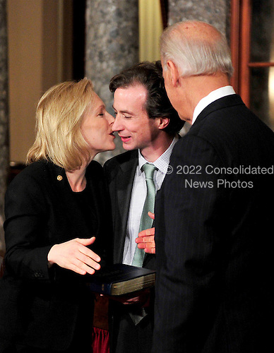 United States Senator Kirsten Gillibrand (Democrat of New York), left, kisses her husband Jonathan, center, during the photo-op of the reenactment of her swearing-in in the Old Senate Chamber in the U.S. Capitol in Washington, D.C. on Wednesday, January 5, 2011.  U.S. Vice President Joe Biden, right, looks on..Credit: Ron Sachs / CNP.(RESTRICTION: NO New York or New Jersey Newspapers or newspapers within a 75 mile radius of New York City)