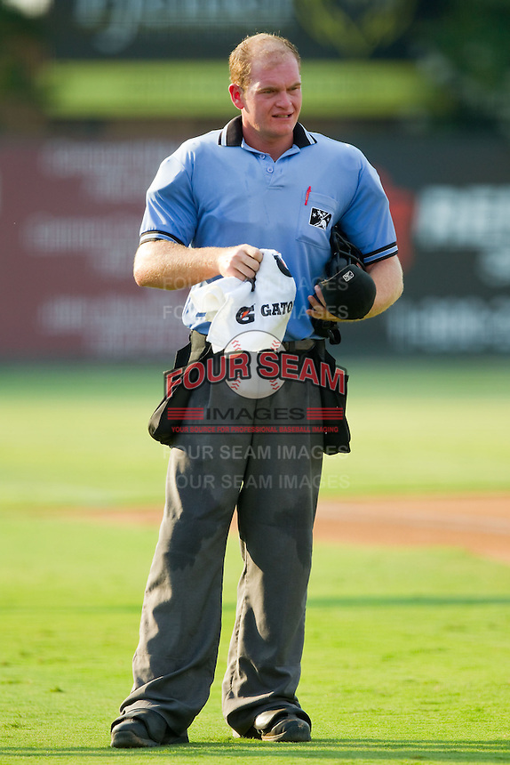 Home plate umpire Jake Wilburn towels off between innings of the South Atlantic League game between the Hickory Crawdads and the Kannapolis Intimidators at CMC-Northeast Stadium on July 28, 2013 in Kannapolis, North Carolina.  The Crawdads defeated the Intimidators 6-1.  (Brian Westerholt/Four Seam Images)