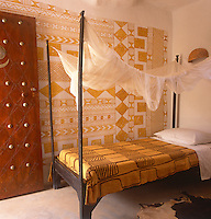 A simple guest bedroom in the Hotel Djenne Djenno A rustic wooden four poster bed with a traditional Bogolan textile bed cover. The Bogolan pattern is continued on the painted wall behind.