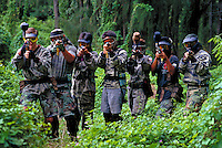 Young men with paintball guns aimed at the viewer out in the jungle