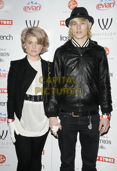 KELLY OSBOURNE & LUKE WORRALL.The Whiteleys Pop-Up Boutique Floor launch party, Whiteleys Shopping Centre, Queensway, London, England..March 25th, 2010.half length white top leather jacket black  gloves holding hands couple 3/4 safety pins belt.CAP/CAN.©Can Nguyen/Capital Pictures.