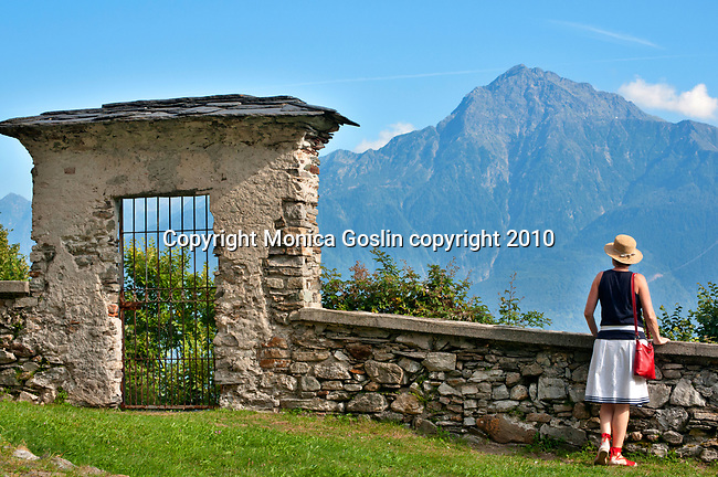 A woman wearing a straw hat admires the view outside of the church of San Giacomo Vecchia in the mountain tow of Livo, just above Gravedona on Lake Como, Italy