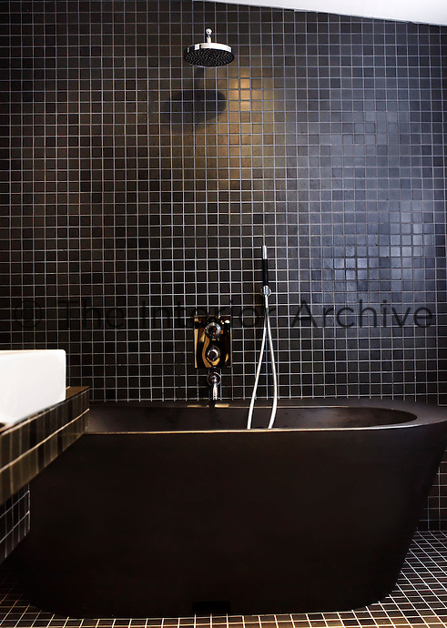 A bath tub made of recycled plastic dominates this black mosaic-tiled bathroom