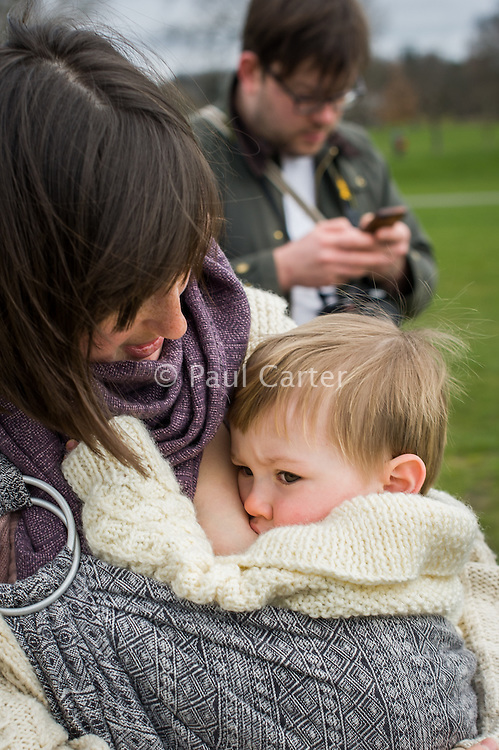 A mother breastfeeds her 15 month old boy from a sling while walking in park. Her husband is texting in the background.<br /> <br /> London, England, UK<br /> 22-03-2015<br /> <br /> &copy; Paul Carter / wdiip.co.uk