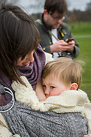 A mother breastfeeds her 15 month old boy from a sling while walking in park. Her husband is texting in the background.<br /> <br /> London, England, UK<br /> 22-03-2015<br /> <br /> © Paul Carter / wdiip.co.uk