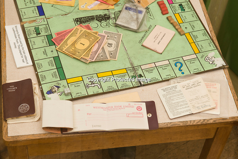 BNPS.co.uk (01202 558833)<br /> Pic: RachelAdams/BNPS<br /> <br /> Pictured: The Monopoly board found during the police raid displayed alongside a cheque book and RogerCondrey's driving licence at the Thames Valley Police Museum, Reading. <br /> <br /> A Monopoly set famously played by the Great Train Robbers using real money while lying low at a farm after there £2.6 million heist has emerged 50 years after the infamous event.<br /> <br /> The tatty board game came to light after it was brought to the Antiques Roadshow for valuation, revealing the little-known story of its part in the 20th century's most notorious heist.<br /> <br /> It was discovered by police in a farmhouse hideout days after the brazen hold-up on a Royal Mail train in 1963.<br /> <br /> The train had been travelling from Glasgow to London but was set upon at Ledburn in Buckinghamshire by the gang, who had tampered with signals.<br /> <br /> The robbers stormed the train and took all but seven of 128 highly-prized sacks worth a total of £2.6 million - the equivalent of nearly £50 million nowadays.<br /> <br /> Following the robbery the gang, including ringleader Bruce Reynolds, Buster Edwards and Ronnie Biggs - retreated to a nearby farmhouse to avoid police.<br /> <br /> There they played the board game to pass the time and would use real money to buy 'property'.