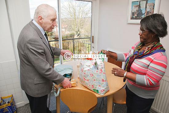 Carer unloading shopping for pensioner.