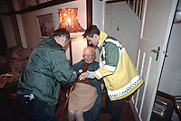 Paramedic ambulance crew attending to an elderly patient who has fallen over at home and has suffered slight head injuries. They have placed her in a stretcher chair to take her to the ambulance. This image may only be used to portray the subject in a positive manner..©shoutpictures.com..john@shoutpictures.com
