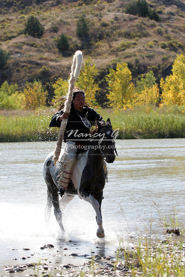 A Native American Sioux Indian on horseback who crossed a river on his Indian Pony and staff in South Dakota