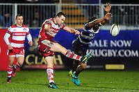 Tom Marshall of Gloucester Rugby boots the ball away as Aled Brew of Bath Rugby looks to charge him down. Anglo-Welsh Cup match, between Bath Rugby and Gloucester Rugby on January 27, 2017 at the Recreation Ground in Bath, England. Photo by: Patrick Khachfe / Onside Images