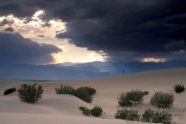 Spring storm clouds at sunset over hiker on sand dunes at sunset, Stovepipe Wells, Death Valley National Park, California