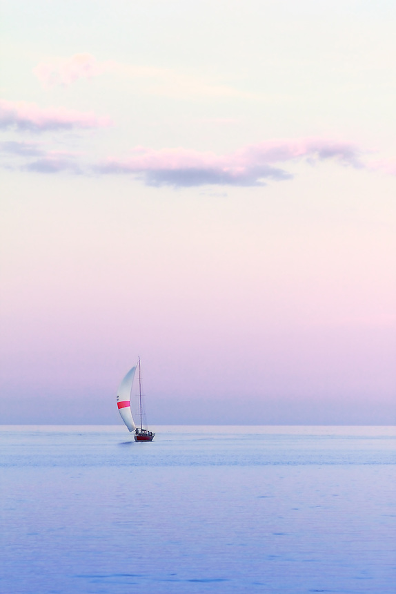 A sailboat on Lake Michigan glides toward the marina in Port Washington, Wisconsin, moments after the sun has set.