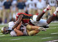 Navy's Vince Murray gets a hand to the face after getting tackled by Terrapins' Kenny Tate. Maryland defeated Navy 17-14 at the M&T Bank in Baltimore, MD on Monday, September 6, 2010. Alan P. Santos/DC Sports Box