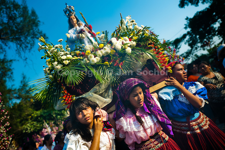 "Salvadoran girls carry an altar with a statue of Virgin Mary during the procession of the Flower & Palm Festival in Panchimalco, El Salvador, 8 May 2011. On the first Sunday of May, the small town of Panchimalco, lying close to San Salvador, celebrates its two patron saints with a spectacular festivity, known as ""Fiesta de las Flores y Palmas"". The origin of this event comes from pre-Columbian Maya culture and used to commemorate the start of the rainy season. Women strip the palm branches and skewer flower blooms on them to create large colorful decoration. In the afternoon procession, lead by a male dance group performing a religious dance-drama inspired by the Spanish Reconquest, large altars adorned with flowers are slowly carried by women, dressed in typical costumes, through the steep streets of the town."