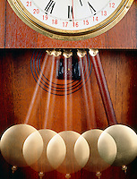 PENDULUM CLOCK: Stroboscopic Regulator Wall Clock (closeup)<br /> The images of the pendulum appear farther apart at the bottom because the bob moves faster at the bottom of the swing and slows down at the top of the swing. Strobed at equal time intervals (20flashes/sec).