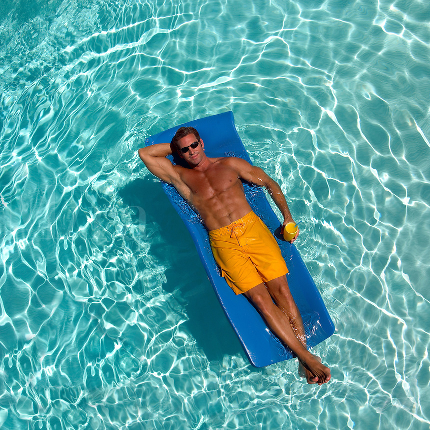 Overhead shot of man in yellow swim trunks, sunglasses, in pool, on blue raft, right arm over head, left hand by side with drink. Model:Thomas Kell