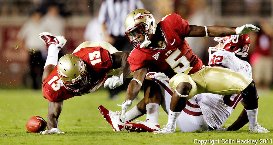 TALLAHASSEE, FL 9/17/11-FSU-OU091711 CH-Florida State's Nigel Bradham and Greg Reid break up a pass meant for Oklahoma's James Hanna during first half action Saturday at Doak Campbell Stadium in Tallahassee. .COLIN HACKLEY PHOTO