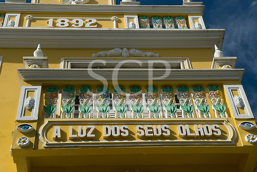 Ilheus, Bahia State, Brazil. Colonial style optician's building in pastel yellow with ornate plaster decoration.