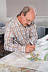 White older man pupil works on scaled drawing for architectural landscaping class in evening schedule